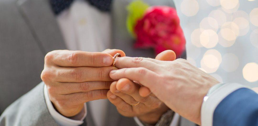 close up of male gay couple hands and wedding ring